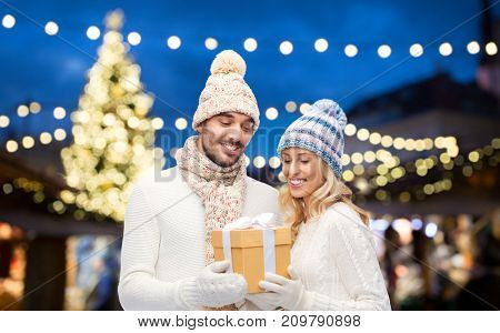 holidays and people concept - happy couple in winter hats with gift box over christmas tree lights background
