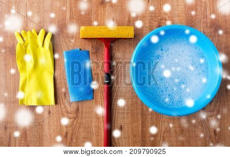 housework, housekeeping and household concept - window cleaning squeegee with rubber gloves, basin and rag on wooden background over snow