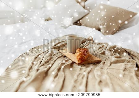 breakfast, cosy home and morning concept - cozy bedroom with coffee cup and croissant on wooden board in bed over snow