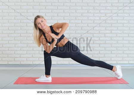 Happy fitness woman sitting on the mat in the gym in yoga pose. Holding two hands together. Wearing sportswear