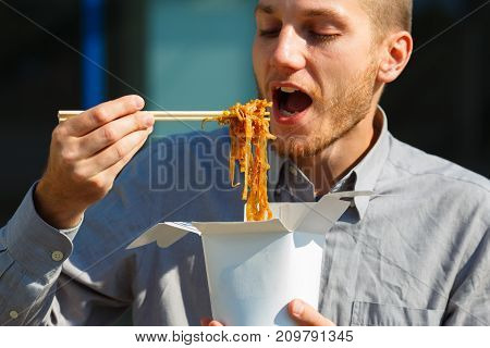 Attractive man eats delicious Chinese egg noodles with vegetables, soy sauce and chili peppers outdoors. Panoramic window on the background. Close-up of nuddle. Food concept.