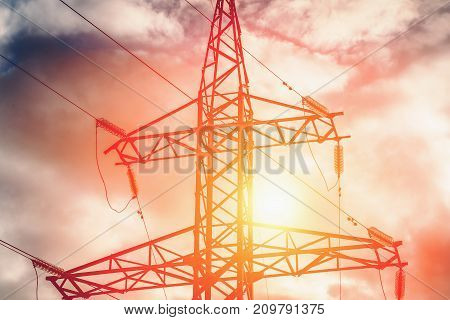 High voltage post or high-voltage tower on sunset sky background, toned