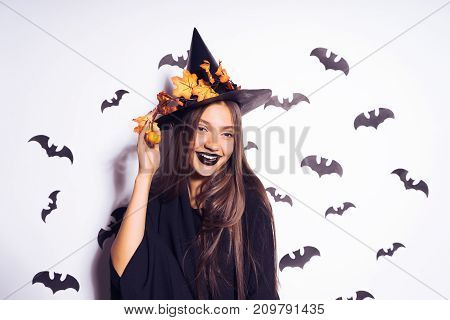 girl in a witch costume posing on a white background