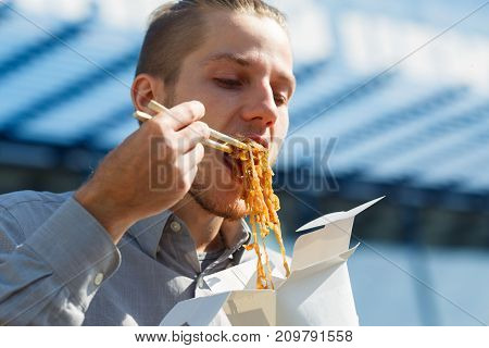 The man eats delicious Chinese egg noodles with vegetables, soy sauce and chili peppers outdoors. Panoramic window on the background. Close-up of nuddle. Food concept.