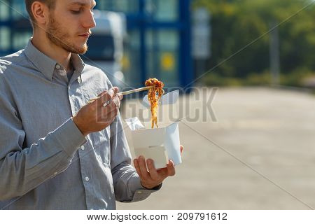 The man eats delicious Chinese egg noodles with vegetables, soy sauce and chili peppers outdoors. Panoramic window on the background. Close-up of man. Food concept.
