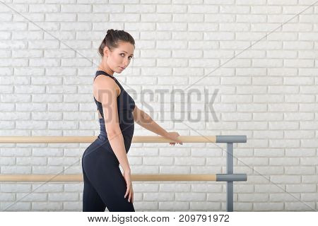 Beautiful ballerina weared in black bodysuit shoes posing at ballet class near barre, three quarter length portrait