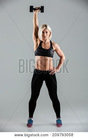 Full length portrait of a concentrated muscular sportswoman doing exercises with a heavy dumbbell isolated over gray background