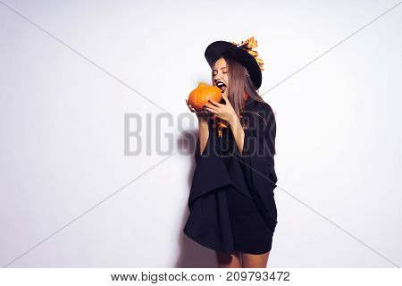 girl in a witch's suit trying to bite a pumpkin