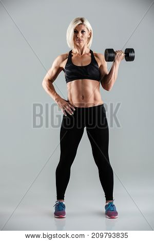 Full length portrait of a concentrated muscular sportswoman working out with a heavy dumbbell isolated over gray background