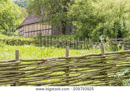 idyllic rural scenery with historic wooden fence and barn at spring time