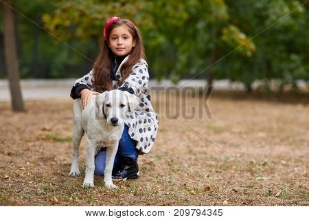 Cute girl kid with doggie walking in the park. Having fun together outdoors on the nature background. Copy space. Animal concept.