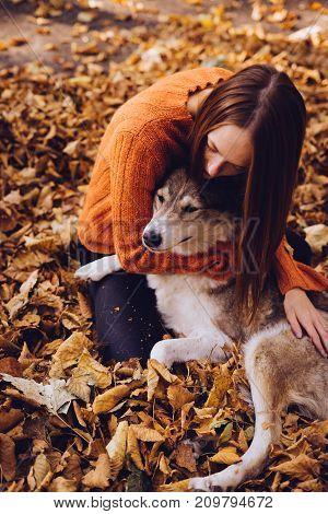 girl lies in a park in fallen leaves hugging her dog
