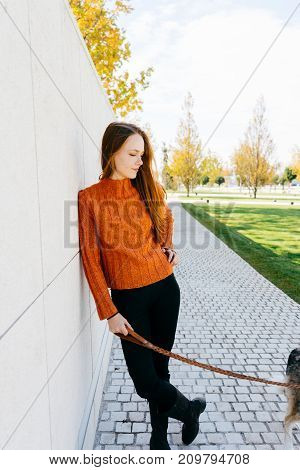 the girl leaned against the wall in the park walking her dog