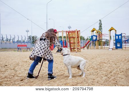 Cute girl kid with doggie playing in the playground. Having fun together outdoors on the nature background. Full length of pet with owner. Animal concept.