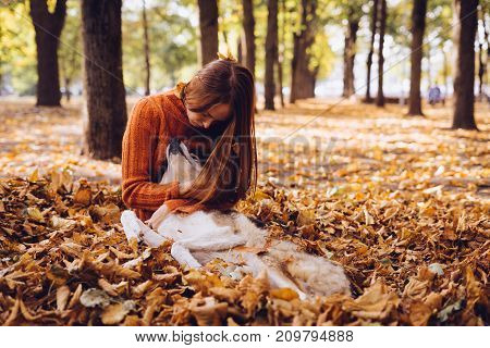 the girl is resting in the autumn foliage with her dog