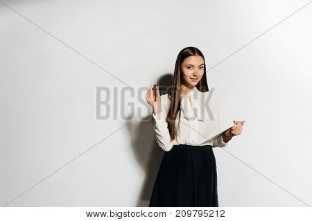girl with a file in her hands holds a coin on a white background