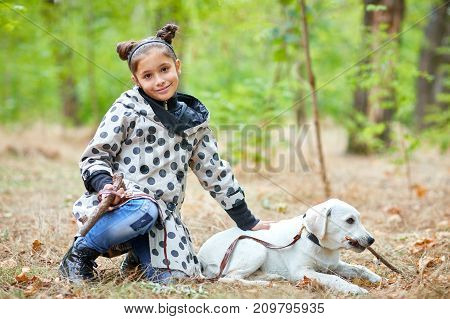 Cute girl with doggie walking in the park. Posing on the camera on the nature background. Full length of girl. Animal concept.