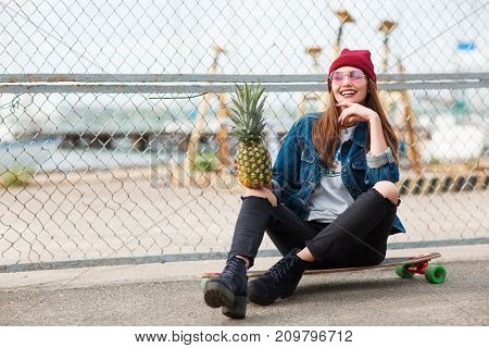 Beautiful young girl in a jeans jacket with glasses sitting on skeatboard with pineapple on the nature background. Close-up of girl.