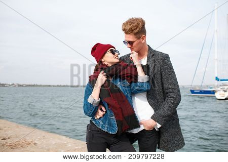 Happy couple in love hugging. Pretty girl in a red cup and attractive man smiling and laughing outdoors. River on the background. Close-up of couple. Copy space.