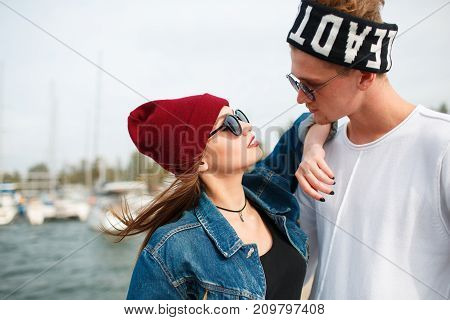 Happy couple in love hugging. Pretty girl in a red cup and attractive man looking on each other outdoors. River on the background. Close-up of couple.