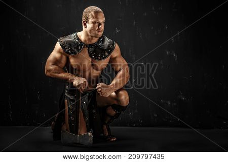 Severe barbarian in leather costume with axe. Studio shot. Black background.
