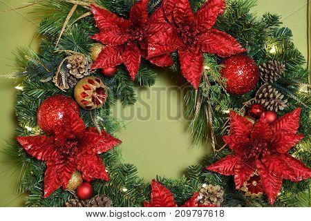 Poinsettia Christmas wreath over green wall