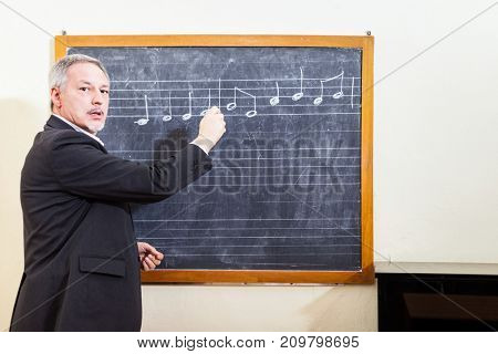 Music teacher writing on a blackboard