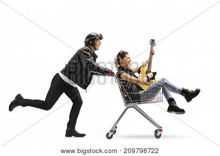 Biker pushing a shopping cart with a punk girl riding inside playing an electric guitar isolated on white background