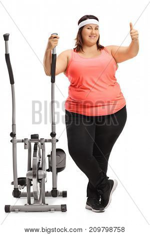 Full length portrait of an overweight woman with a cross trainer machine making a thumb up gesture isolated on white background