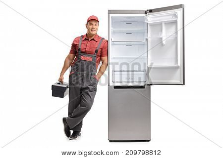 Full length portrait of a repairman with a toolbox leaning against an open fridge isolated on white background