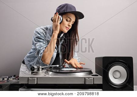 Female DJ playing music on a turntable against a gray wall