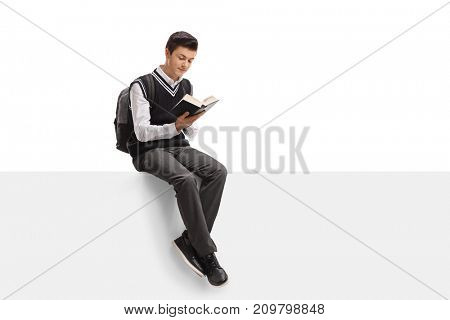 Teenage student sitting on a panel and reading a book isolated on white background
