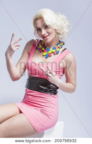 Fashion Ideas and Concepts. Sexy Caucasian Blond Female in Pink Short Dress and Sneakers. Sitting on White Prop and Showing V-Sign. Over White Background.Vertical Image