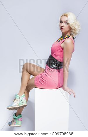 Natural Portrait of Sensual Caucasian Blond Female in Pink Short Dress and Sneakers. Sitting on White Prop. Over White. Vertical Image Orientation