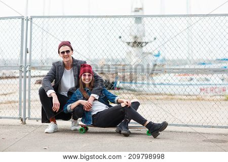 Pretty girl in a red cup sitting on a skateboard and handsome boy hugging a girl on the nature background. Copy space. Full length of girl.