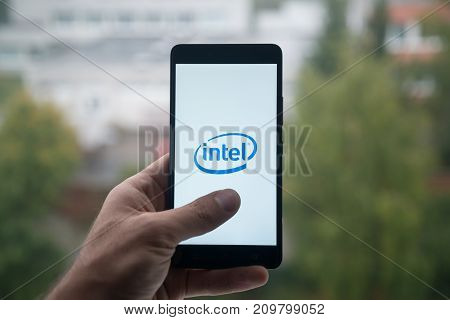 London, United Kingdom, october 3, 2017: Man holding smartphone with Intel logo with the finger on the screen