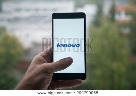 London, United Kingdom, october 3, 2017: Man holding smartphone with Lenovo logo with the finger on the screen