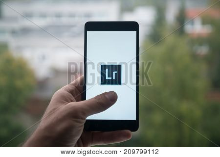 London, United Kingdom, october 3, 2017: Man holding smartphone with Adobe photoshop lightroom logo with the finger on the screen