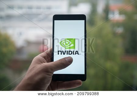 London, United Kingdom, october 3, 2017: Man holding smartphone with Nvidia logo with the finger on the screen