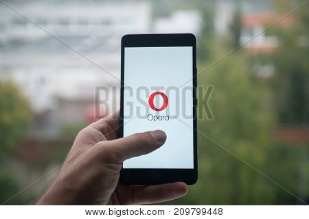 London, United Kingdom, october 3, 2017: Man holding smartphone with Opera mini logo with the finger on the screen