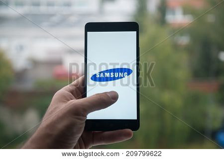 London, United Kingdom, october 3, 2017: Man holding smartphone with Samsung logo with the finger on the screen