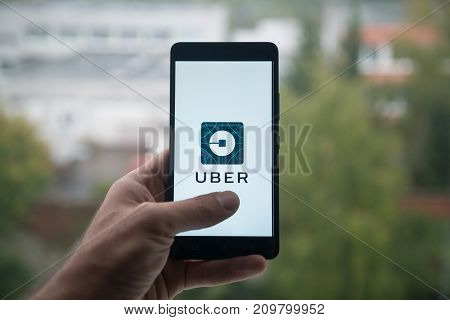 London, United Kingdom, october 3, 2017: Man holding smartphone with Uber logo with the finger on the screen