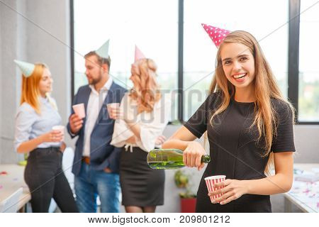 A group of office workers are happy with the holiday that they celebrate all raise their hands, smile pour champagne