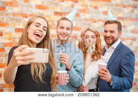 A company of office workers photographed on holiday with drinks and smiling