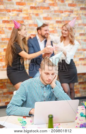 The employee works for a laptop on the background of celebration of the holiday company in hats with smiles