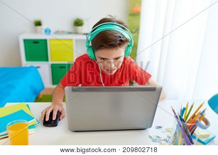 cyberbullying, gaming and people concept - boy in headphones playing video game on laptop computer at home
