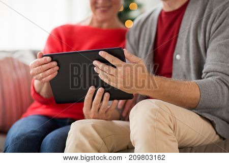 christmas, holidays and people concept - close up of happy smiling senior couple with tablet pc computer at home