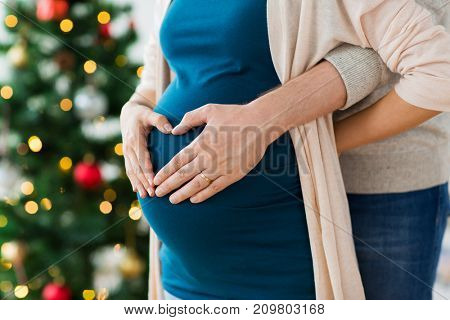 pregnancy, winter holidays and people concept - close up of man making hand heart gesture on his pregnant wife belly at christmas