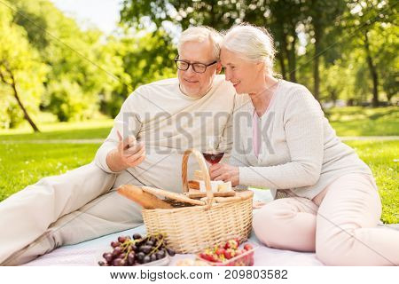 old age, holidays, leisure and people concept - happy senior couple with smartphone, picnic basket and wine sitting on blanket at summer park