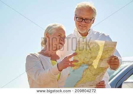 road trip, travel and old people concept - senior couple at car looking for location on map in summer
